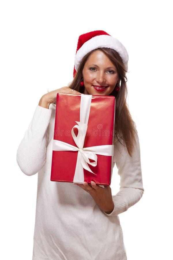 Mooie vrouw in een Kerstmanhoed met een grote gift stock afbeeldingen