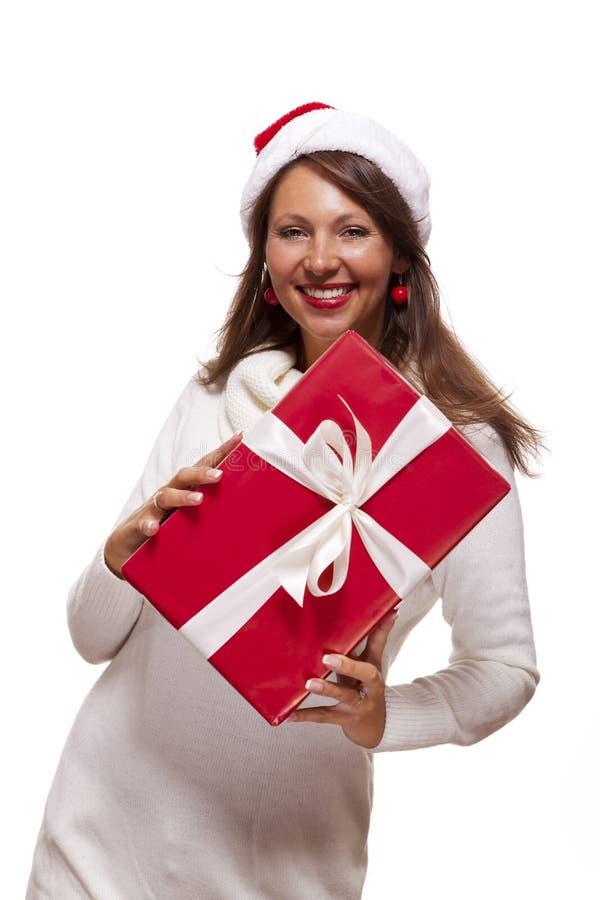 Mooie vrouw in een Kerstmanhoed met een grote gift stock afbeelding