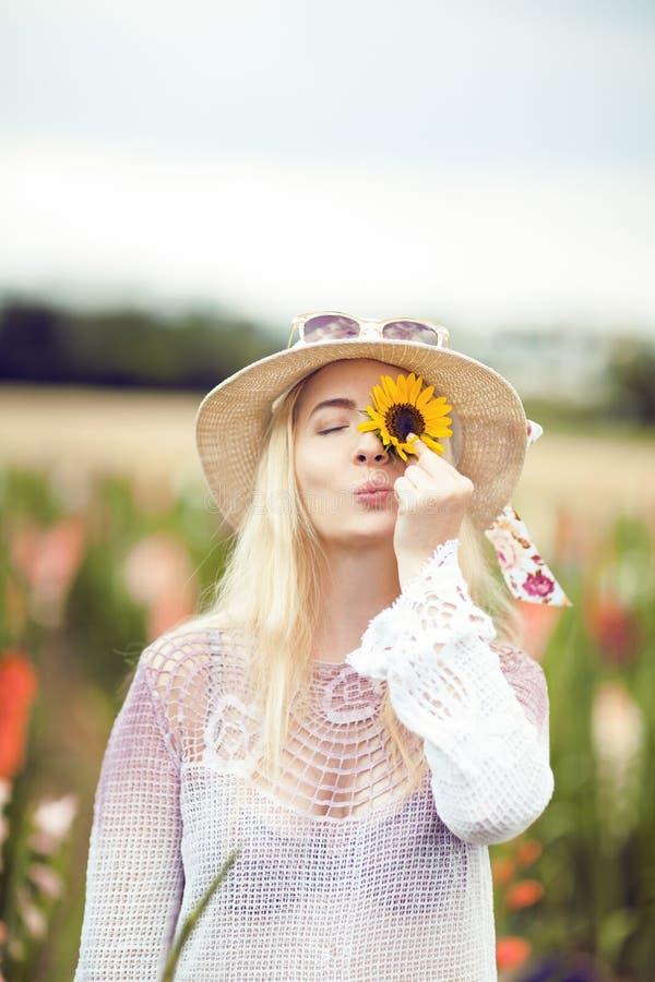 Mooie vrouw in een landelijke gebiedsscène in openlucht, met zonnebloem en sunhat stock foto's