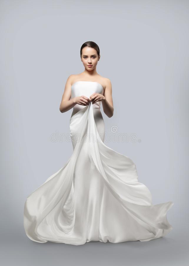 Mooie vrouw in een licht die witte kleding fladderen Lichte stoffenvliegen in de wind Lichtgrijze achtergrond stock fotografie