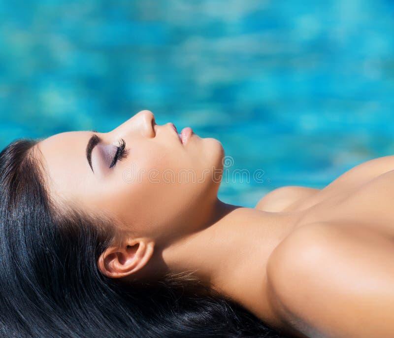 Mooie vrouw in een openluchtpool Kuuroordportret stock foto