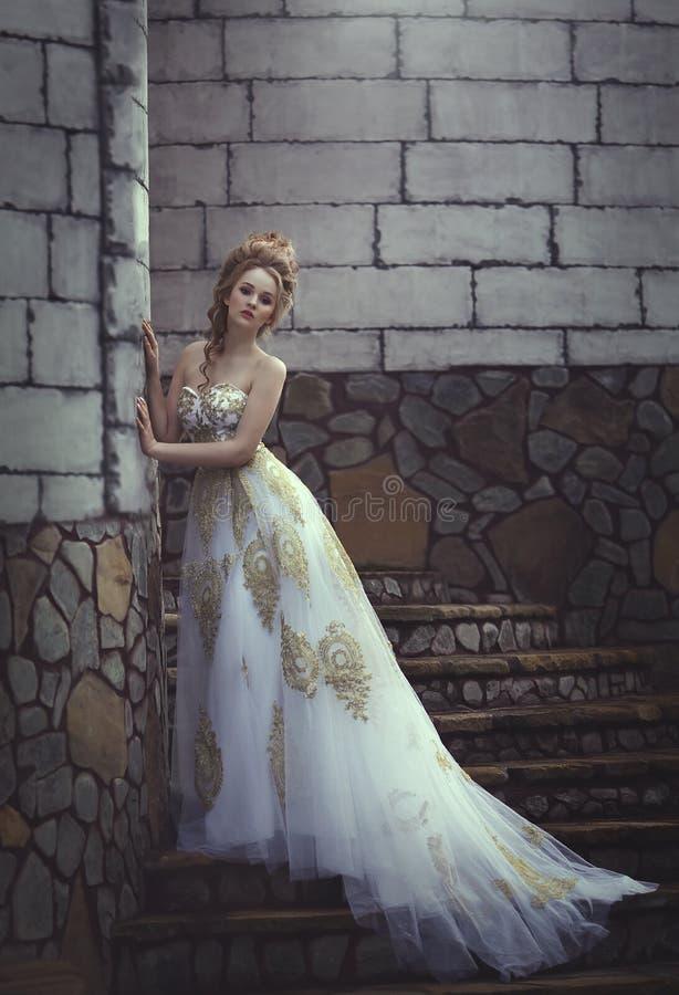 Mooie vrouw in een oude middeleeuwse kleding, met een hoog complex historisch kapsel dichtbij de muren van het kasteel stock foto
