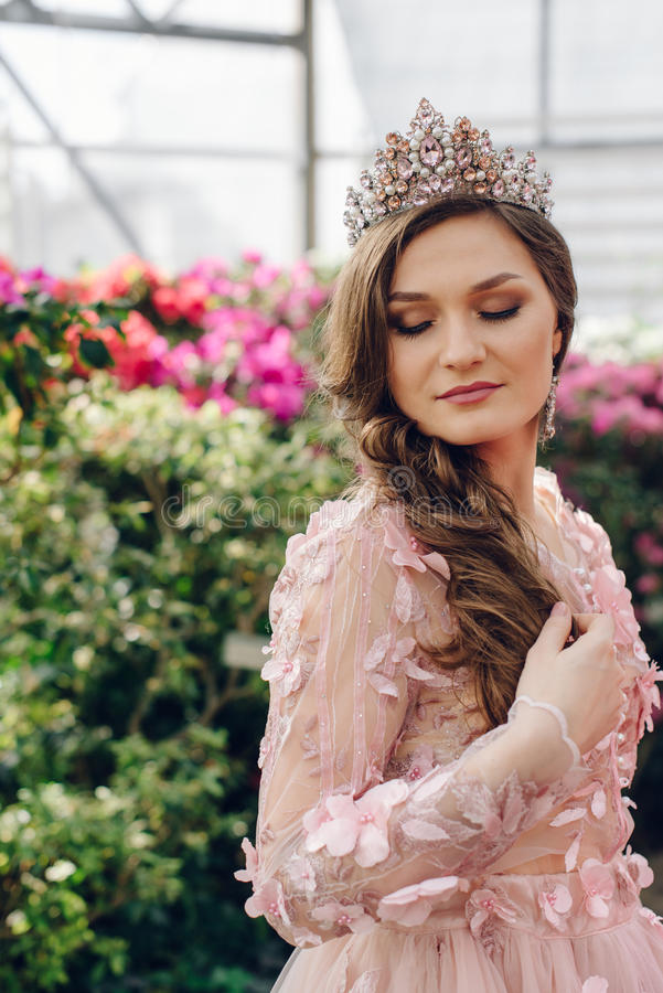 Mooie vrouw in een perzik-gekleurde kleding in een bloeiende tuin royalty-vrije stock foto's