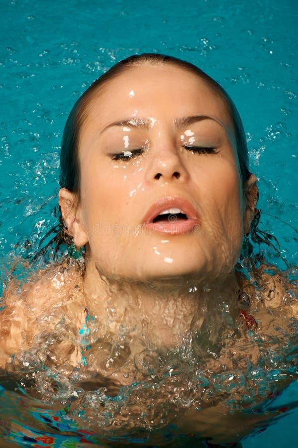 Mooie vrouw in een zwembad. stock afbeeldingen