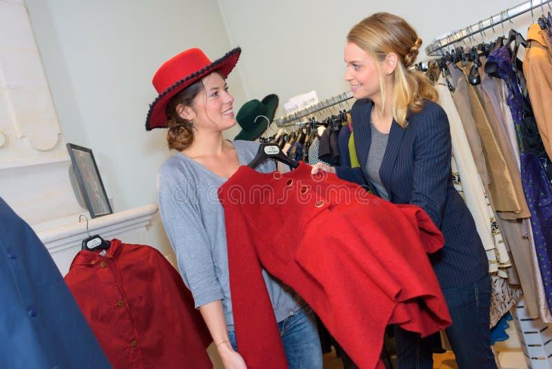 Mooie vrouw en vriend die op kleren in winkel proberen stock foto