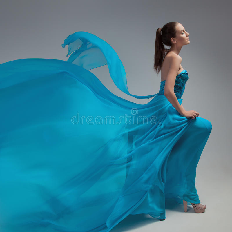 Mooie vrouw in fladderende luchtige blauwe kleding Grijze achtergrond royalty-vrije stock afbeeldingen