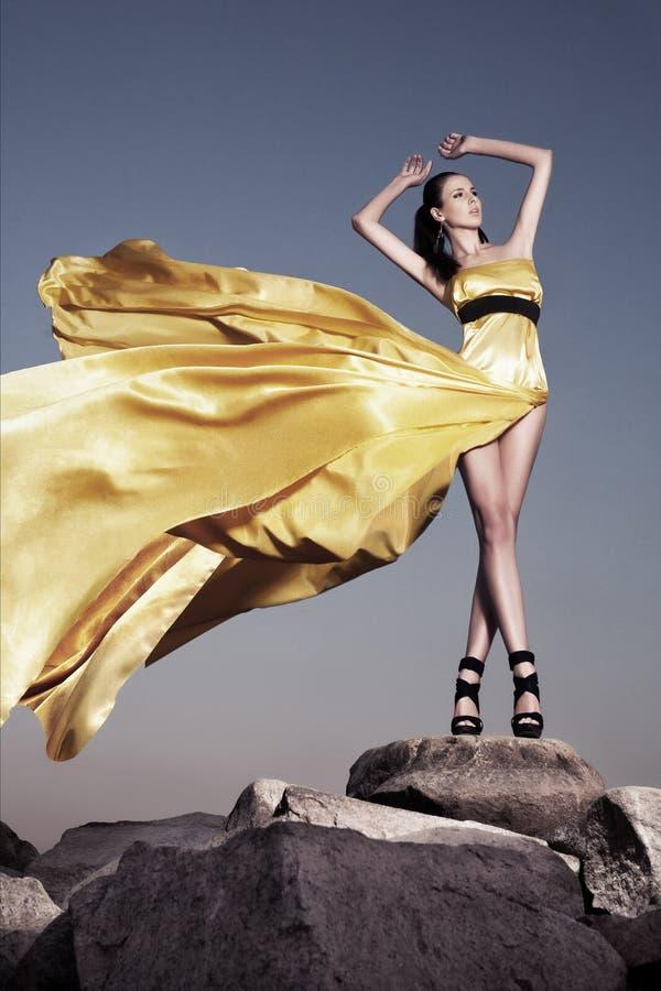 Mooie vrouw in gele avondjurk stock afbeeldingen
