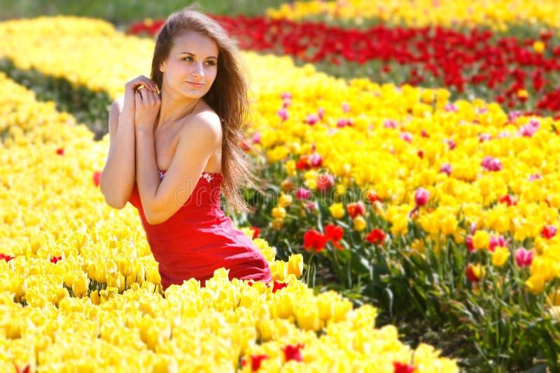 Mooie vrouw in gele tulpen royalty-vrije stock afbeelding