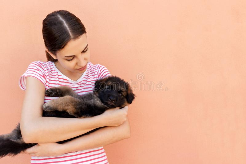 Mooie vrouw in gestreept T die kleine hond houden royalty-vrije stock afbeeldingen