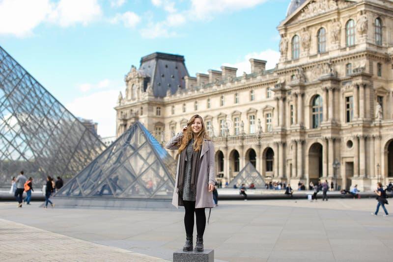 Mooie vrouw grijze laag dragen en zich dichtbij Louvre bevinden en glaspiramide die in Parijs royalty-vrije stock afbeelding