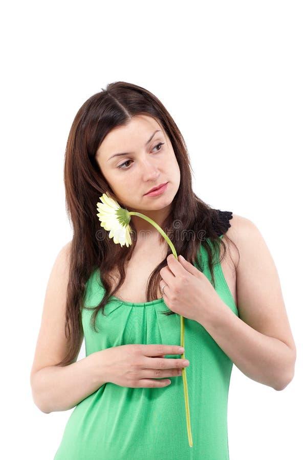 Mooie vrouw in groene kleding met gerbera over wit royalty-vrije stock afbeeldingen