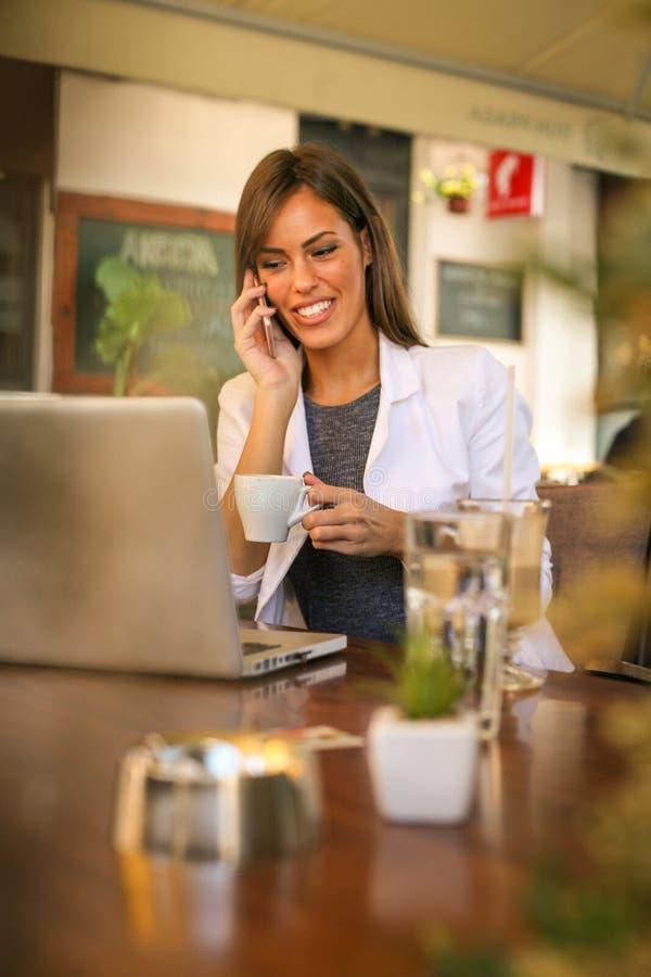 Mooie vrouw het drinken koffie, die op telefoon spreken stock afbeelding