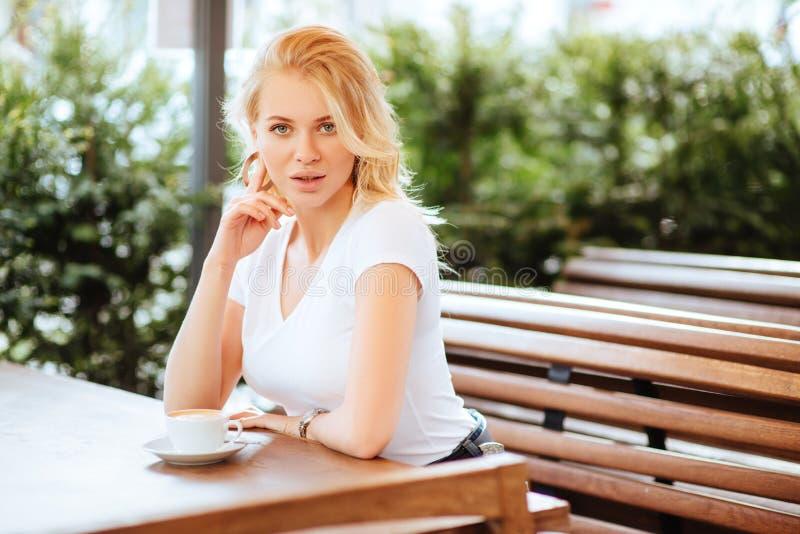 Mooie vrouw het drinken koffie in een koffie royalty-vrije stock afbeeldingen