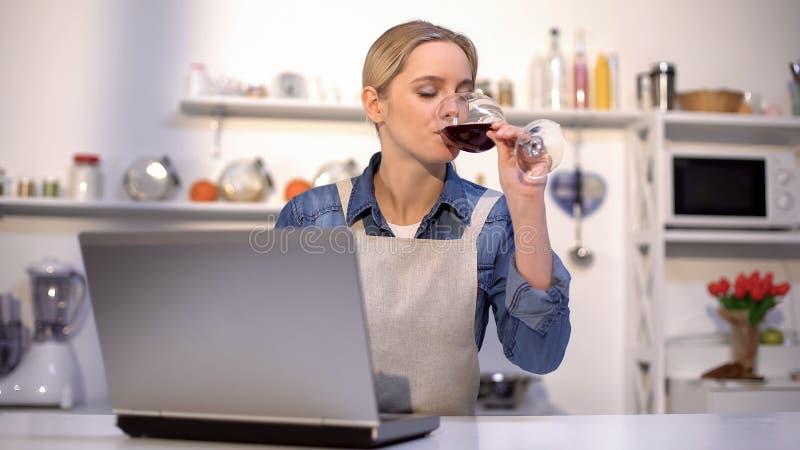 Mooie vrouw het drinken wijn en het zoeken van voedselrecepten naar romantisch diner royalty-vrije stock fotografie