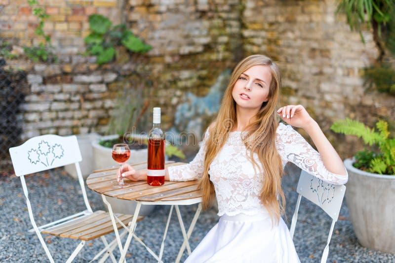 Mooie vrouw het drinken wijn in in openlucht koffie Portret die van jonge blondeschoonheid in de wijngaarden die pret hebben, van stock afbeelding