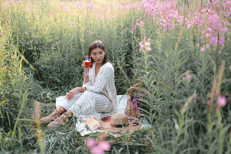 Mooie vrouw het drinken wijnstok op een gebied met bloemen De zomerlevensstijl Picknick stock foto's