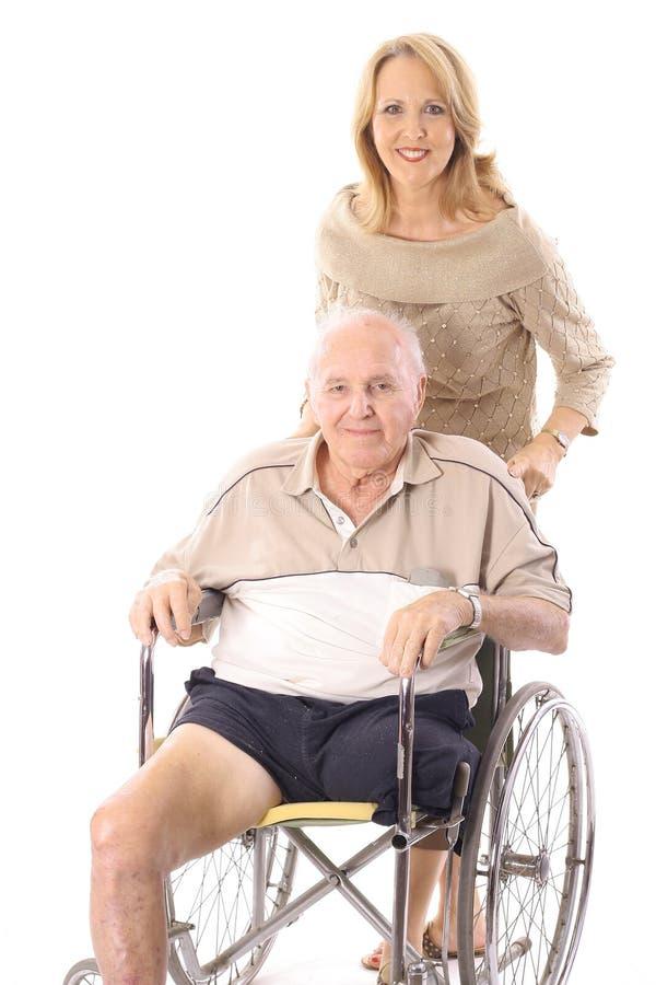 Mooie vrouw het duwen handicapman verticaal stock afbeelding