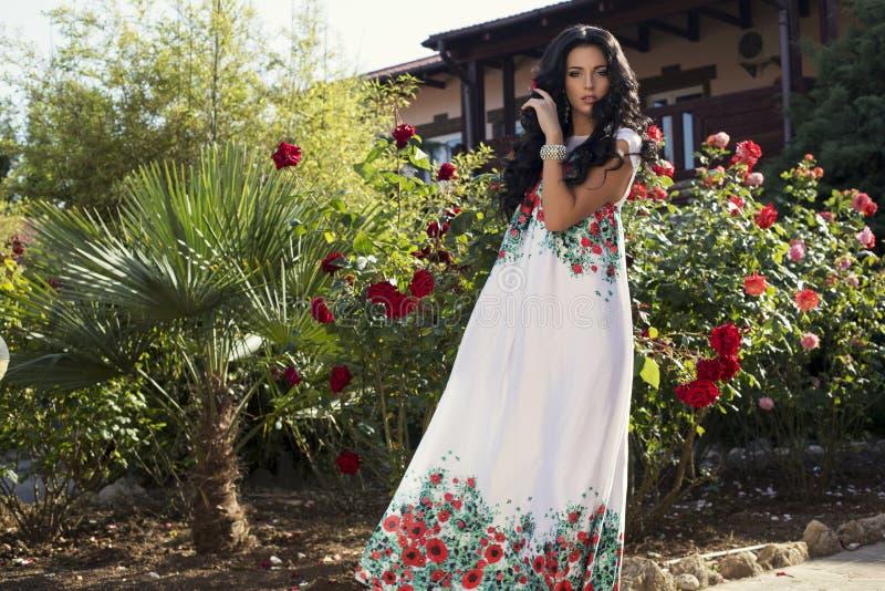 Mooie vrouw in het elegante kleding stellen bij de tuin van de villa royalty-vrije stock fotografie