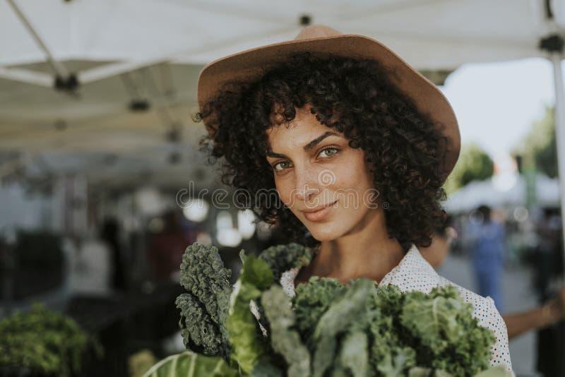 Mooie vrouw het kopen boerenkool bij een landbouwersmarkt stock fotografie