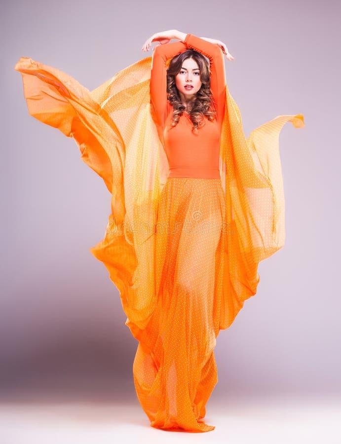 Mooie vrouw in het lange oranje kleding stellen dramatisch in de studio stock foto's