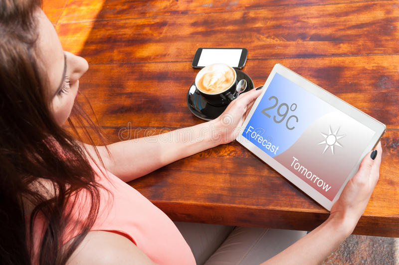 Mooie vrouw het letten op voorspelling op haar tablet royalty-vrije stock foto