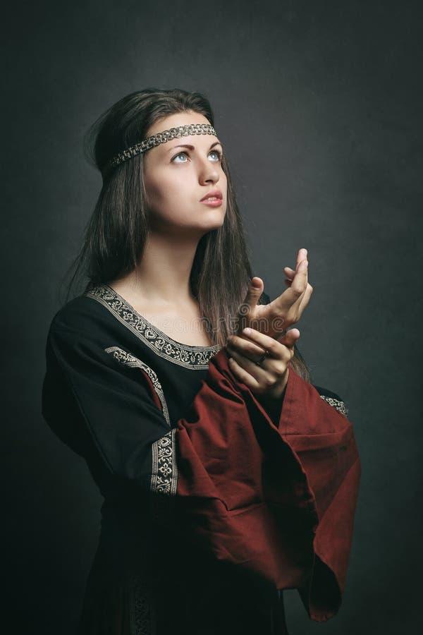 Mooie vrouw in het middeleeuwse kleding bidden stock afbeelding