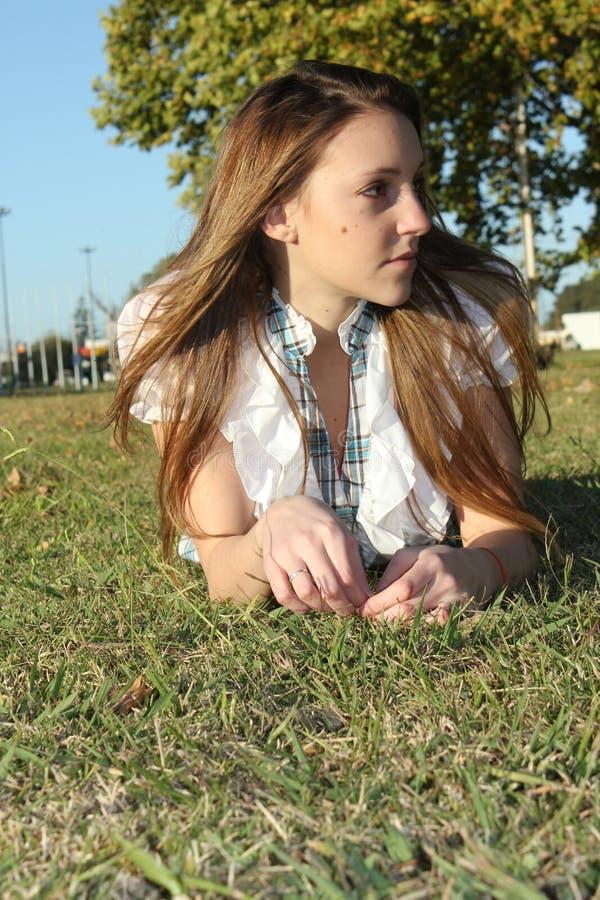 Mooie vrouw in het parkgras stock afbeeldingen
