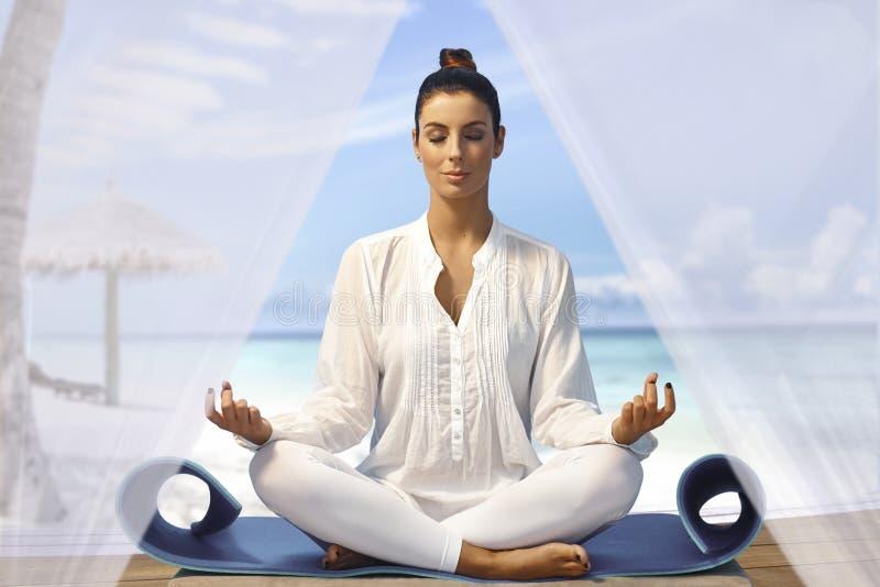 Mooie vrouw het praktizeren yoga op het strand royalty-vrije stock fotografie