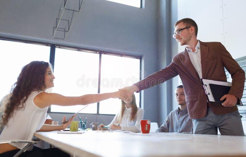 Mooie vrouw het schudden handen met een bedrijfsman op de bureauachtergrond Het concept van de vooruitgang De ruimte van het exem stock fotografie