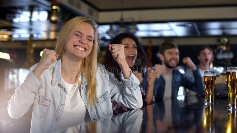 Mooie vrouw het vieren overwinning met vrienden die op sporten in bar, uitzending letten stock foto