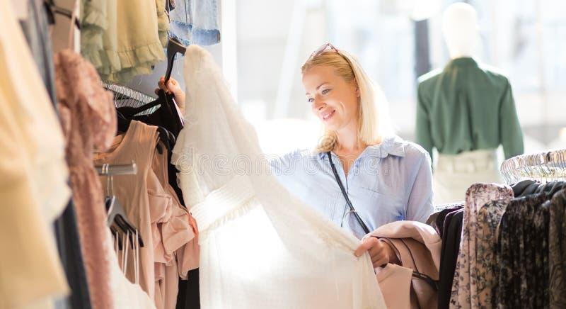 Mooie vrouw het winkelen modieuze kleren in kledingsopslag royalty-vrije stock afbeelding