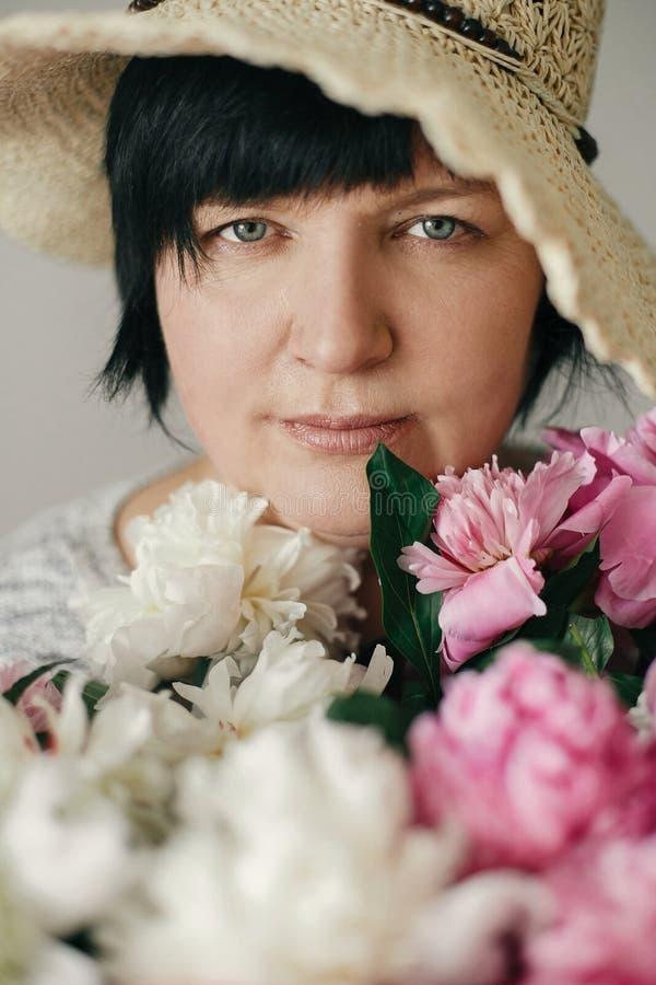 Mooie vrouw in hoed het stellen met vele pioenbloemen Gelukkige moeder met groot boeket van roze pioenen van kinderen Gelukkige m stock foto
