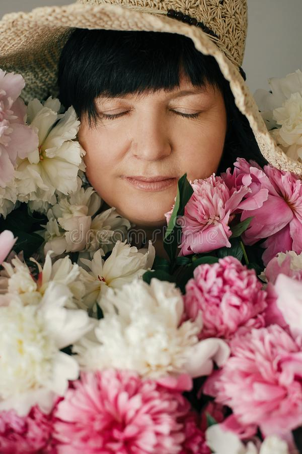Mooie vrouw in hoed het stellen met vele pioenbloemen Gelukkige moeder met groot boeket van roze pioenen van kinderen Gelukkige m stock foto's