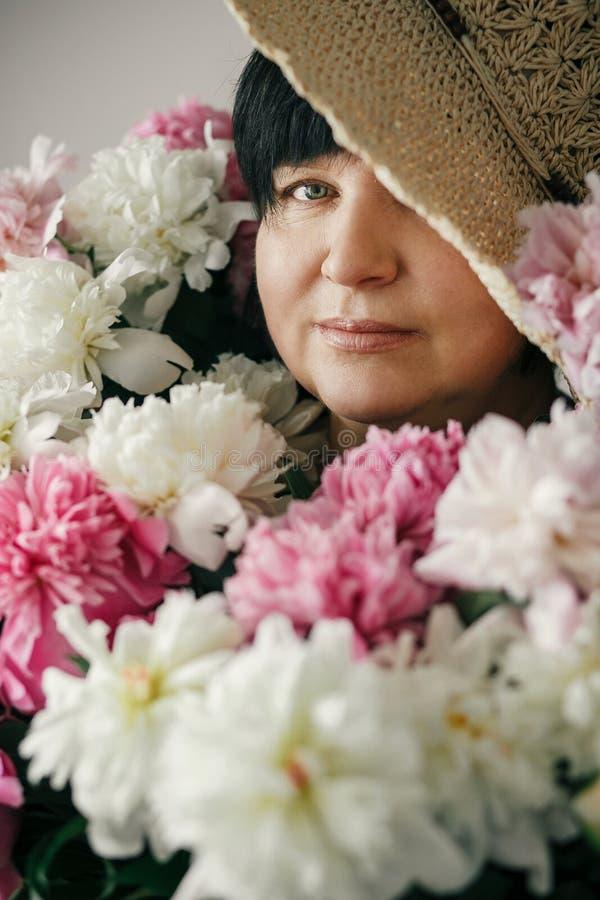Mooie vrouw in hoed het stellen met vele pioenbloemen Gelukkige moeder met groot boeket van roze pioenen van kinderen Gelukkige m stock afbeelding