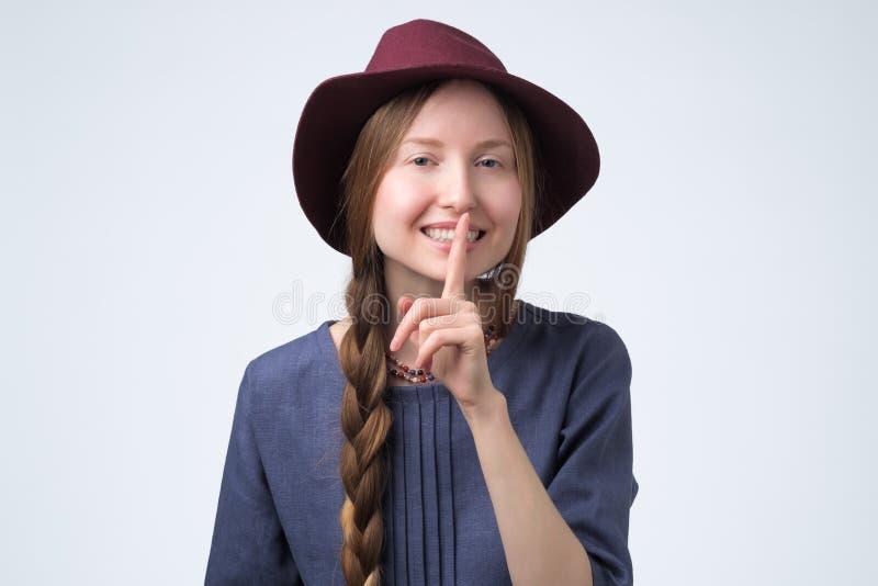 Mooie vrouw in hoed met lange vlecht met vinger op lippen stock fotografie