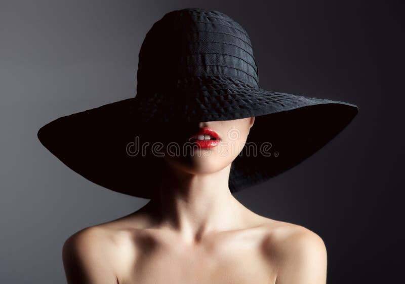 Mooie vrouw in hoed Retro manier Donkere achtergrond stock fotografie