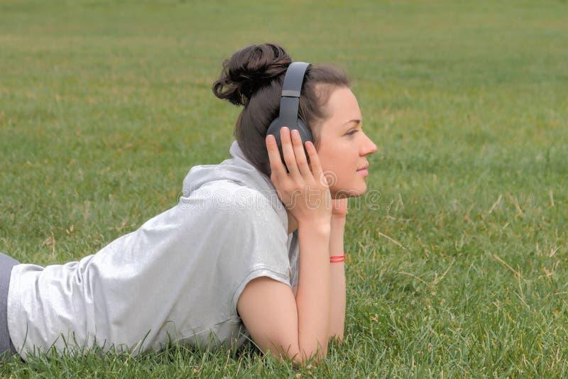 Mooie vrouw in hoofdtelefoons die op groene weide liggen stock afbeelding