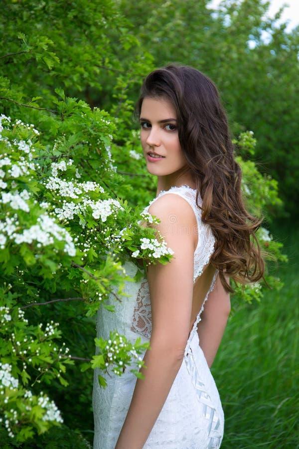 Mooie vrouw in huwelijkskleding in bloeiende tuin stock afbeeldingen