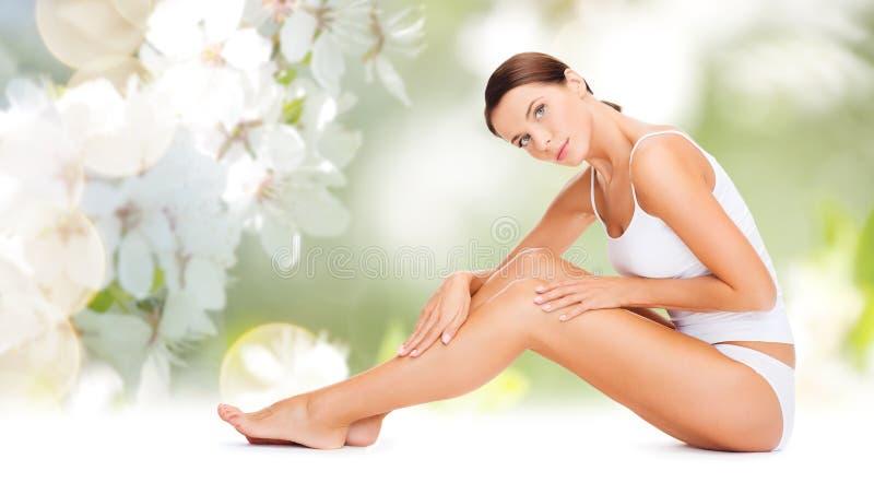 Mooie vrouw in katoenen ondergoed wat betreft benen stock fotografie