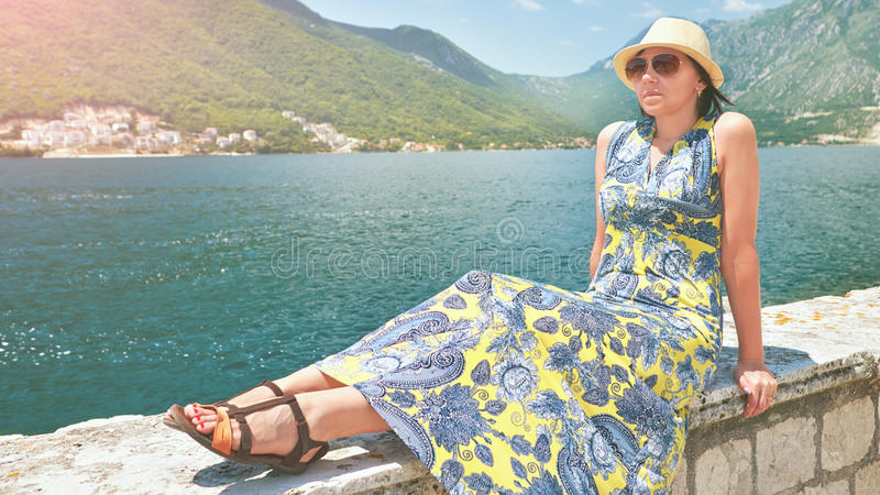 Mooie vrouw in kleding en hoed op kust van eiland Boka Kotorska Montenegro stock foto