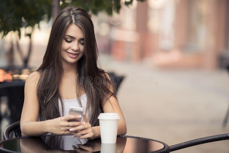 Mooie Vrouw in Koffiewinkel die Sms op Smartphone verzenden stock foto
