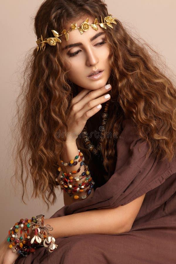 Mooie vrouw Krullend Lang Haar Mannequin in Gouden Kleding Gezond golvend Kapsel toebehoren Autumn Wreath, Gouden Bloemenkroon stock foto's