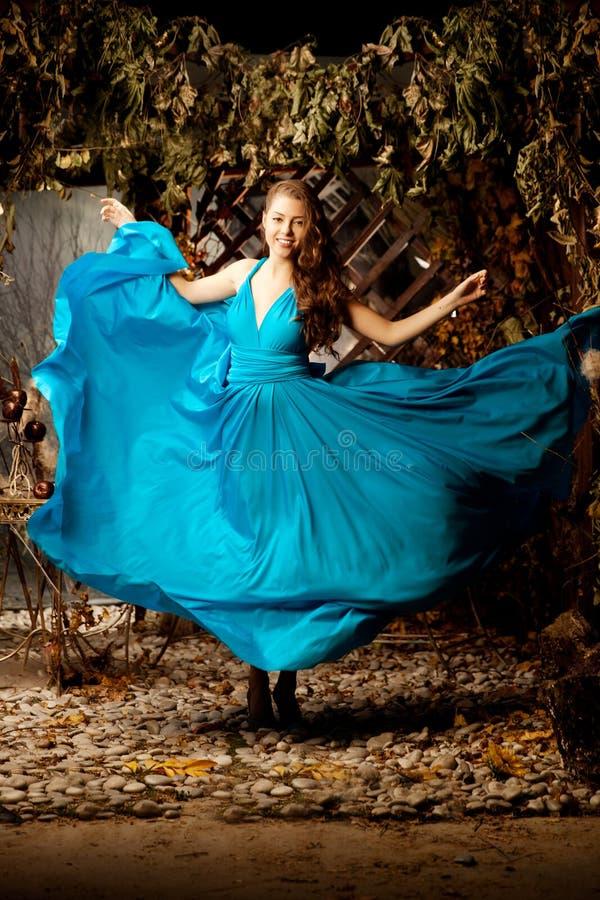 Mooie vrouw in lang blauwe kleding Jong meisje op luxemanier royalty-vrije stock afbeeldingen