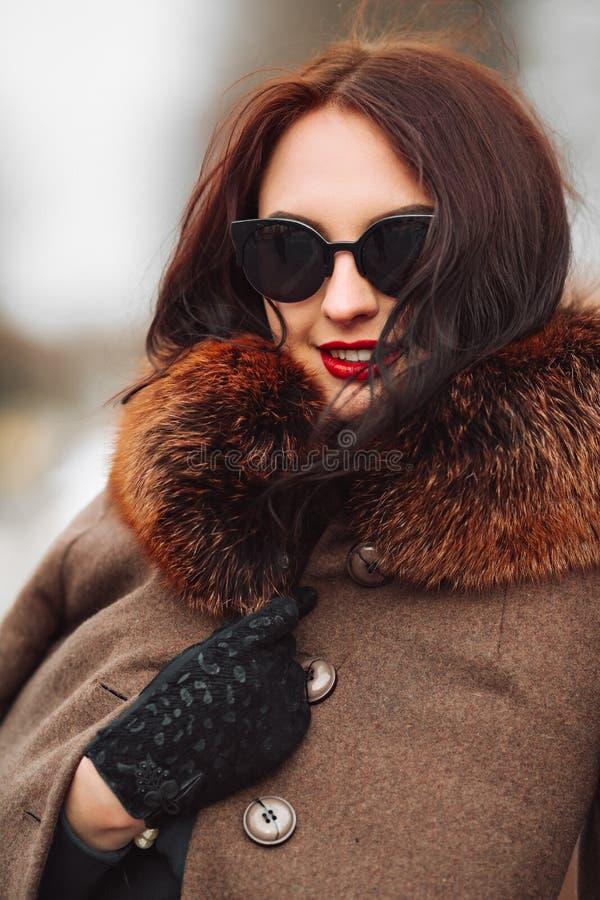 Mooie vrouw in luxebontjas Modieuze donkerbruine vrouw in bruine laag stock afbeeldingen