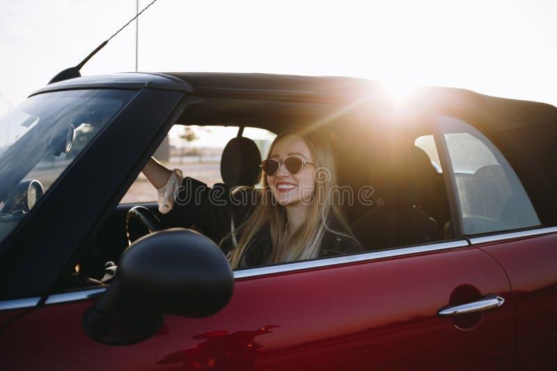 Mooie vrouw in manier convertibele auto op zonsondergang royalty-vrije stock fotografie