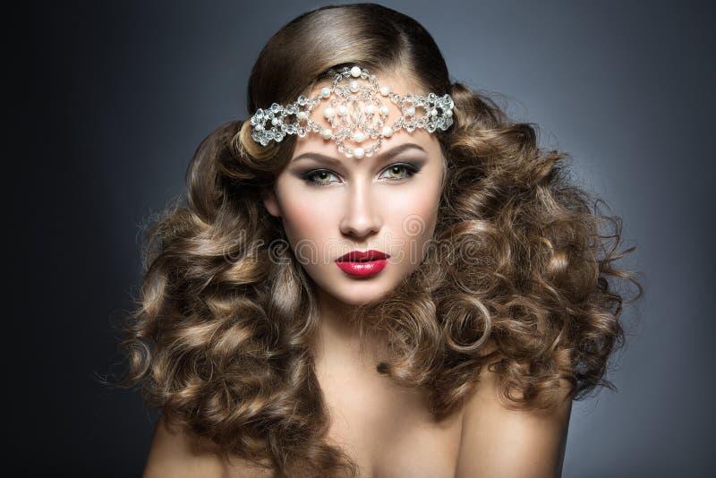 Mooie vrouw met avondsamenstelling en krullen en grote juwelen op haar hoofd Het Gezicht van de schoonheid stock afbeelding