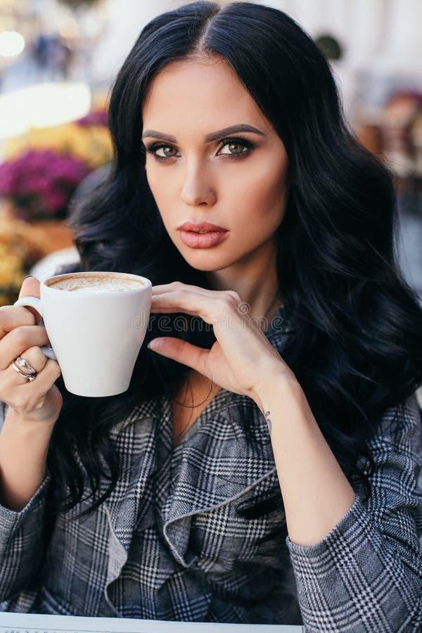 Mooie vrouw met blond haar in elegante kleren die in koffie stellen, die een koffie met dessert drinken royalty-vrije stock afbeelding