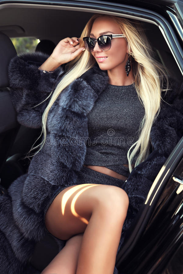 Mooie vrouw met blond haar in elegante uitrusting, die op weg stellen stock foto's