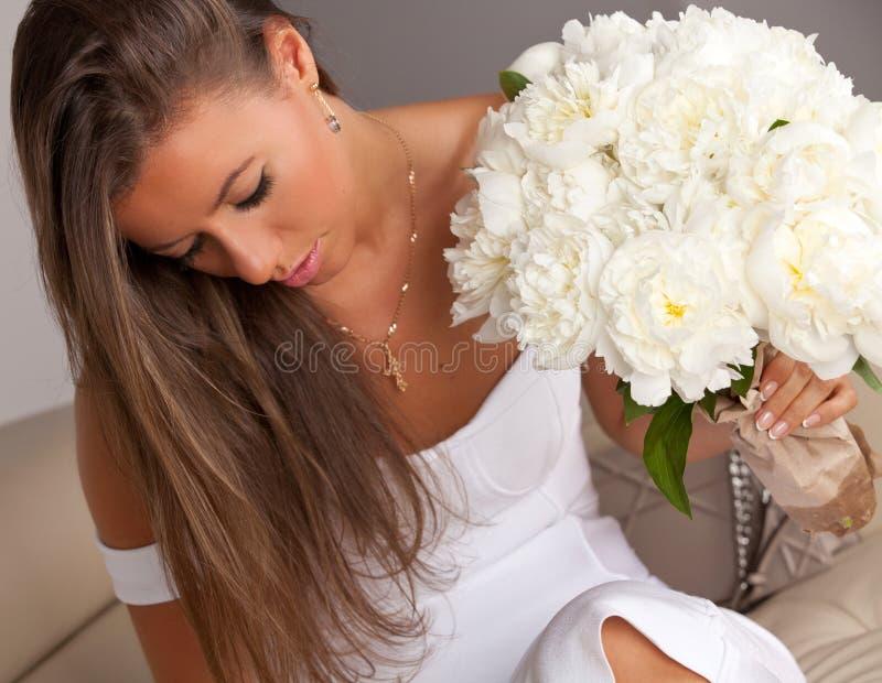 Mooie vrouw met boeket van witte pioenen stock fotografie