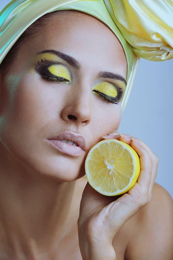 Mooie vrouw met citroen in gele sjaal stock fotografie